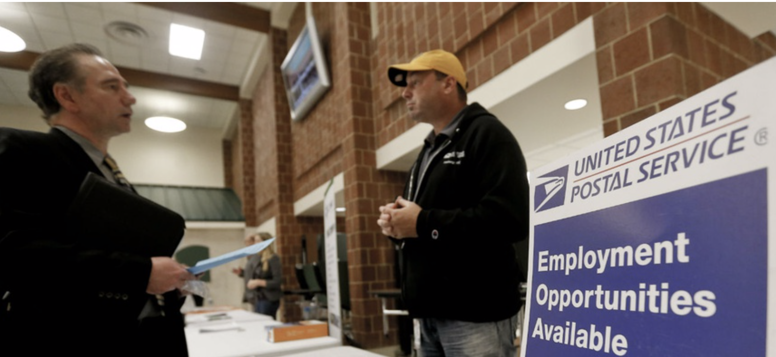 A recruiter with the U.S. Postal Service talks to a prospective job candidate. Studies show that low pay is a deterrent to attracting and retaining supervisors at USPS. AP FILE PHOTO