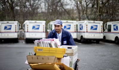 Postal worker pushing a cart full of mail