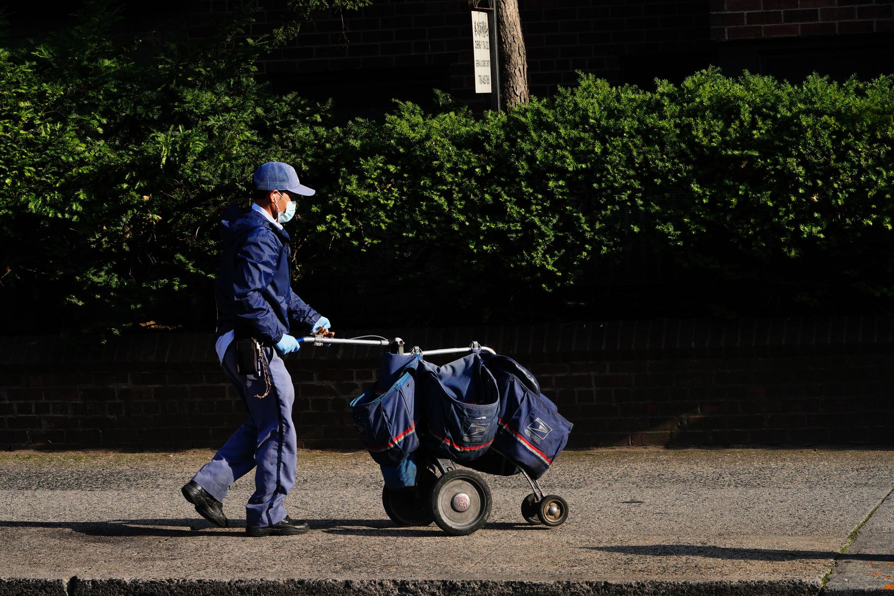 Postal worker wearing face mask pushing mail cart