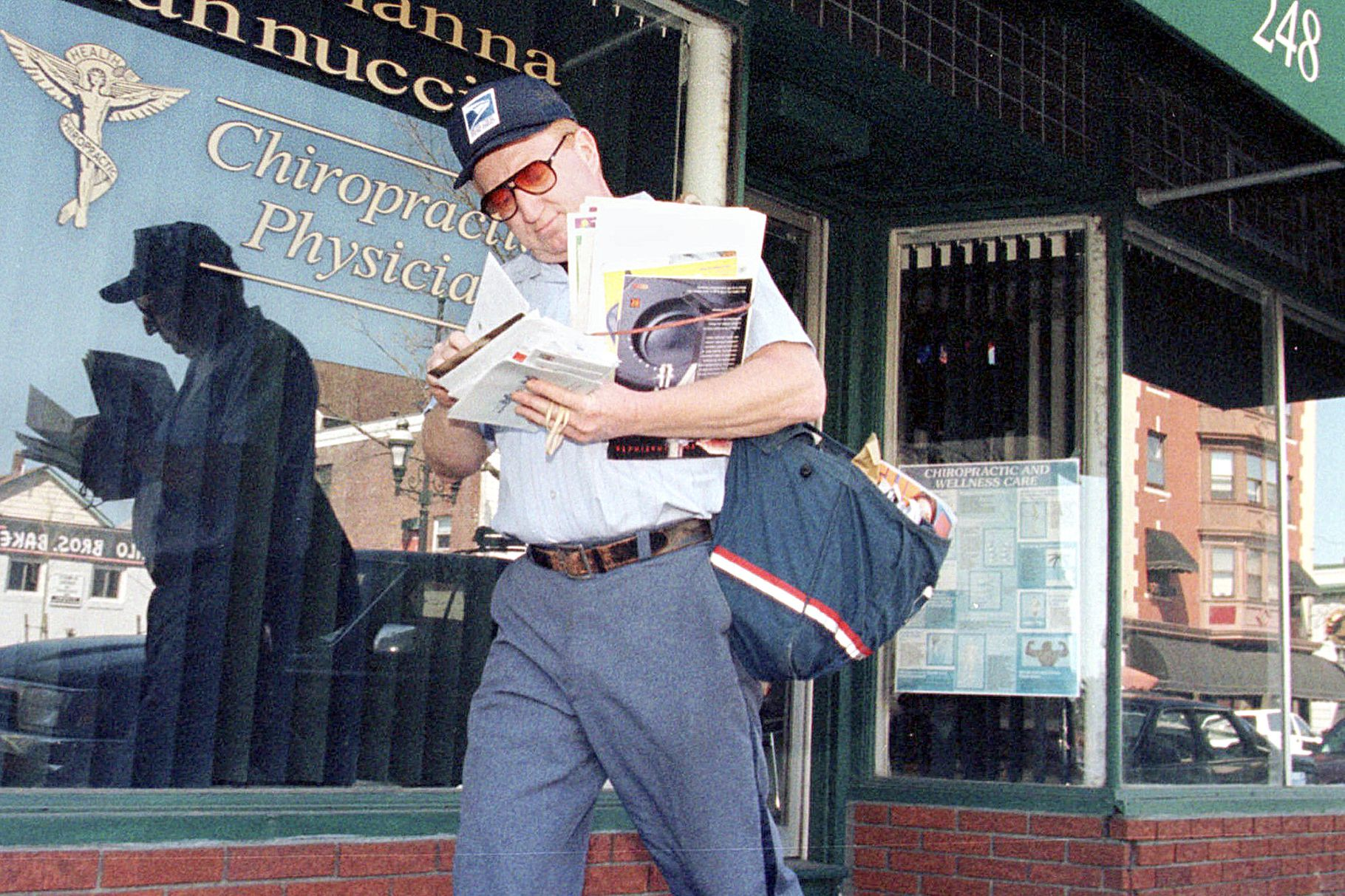 Postal Carrier walking with mail in front of a glass storefront