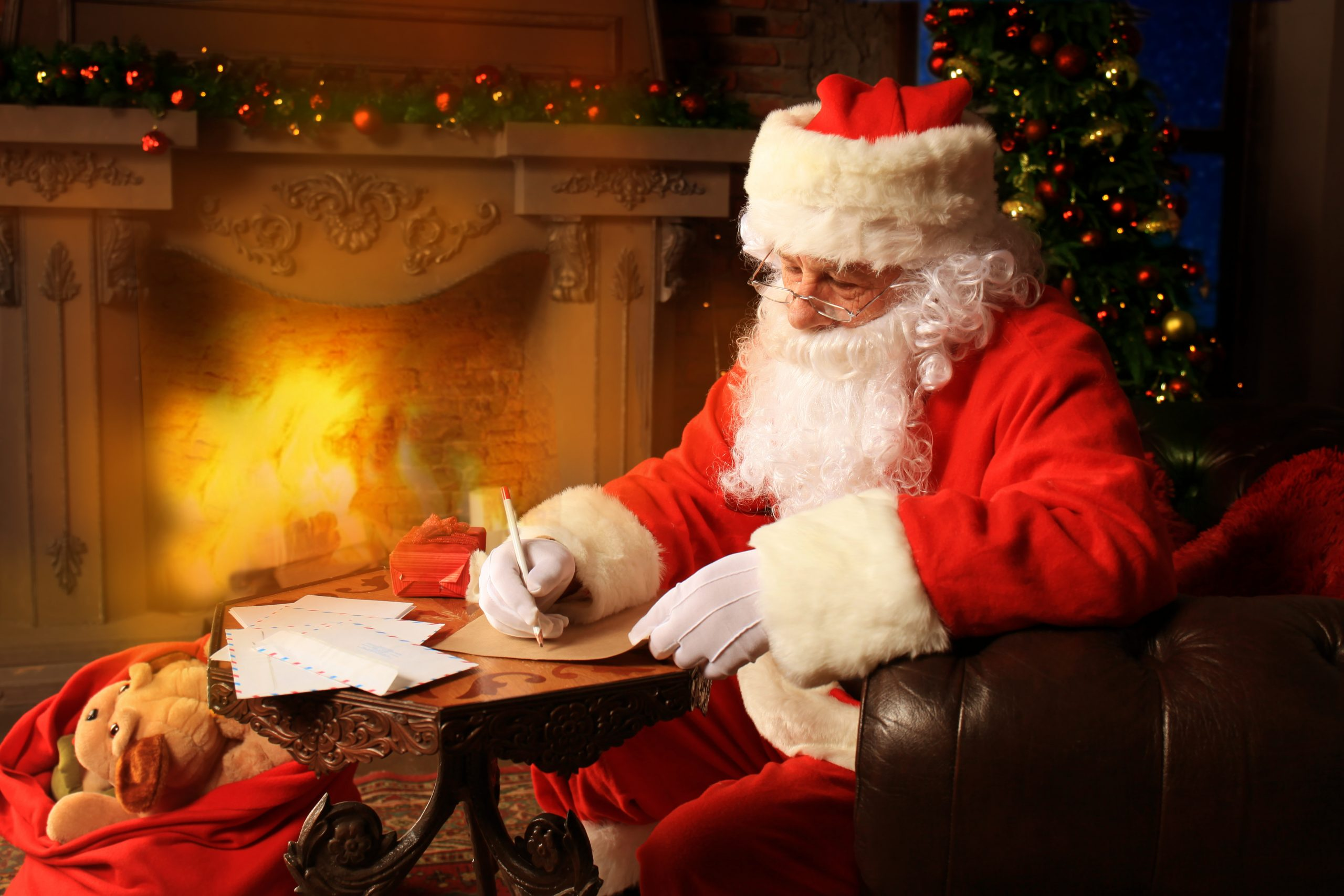 Santa writing letters in front of a fireplace